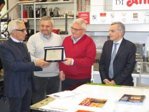 Il presidente di Ascom Enrico Postacchini consegna la targa per i 70 a Gianni e Mauro Guizzardi